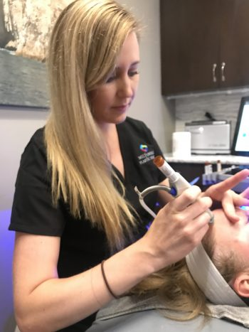 Andrea using a laser on a patients forehead
