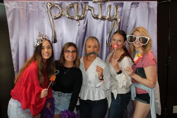 Patients posing with various props in front of a party backdrop